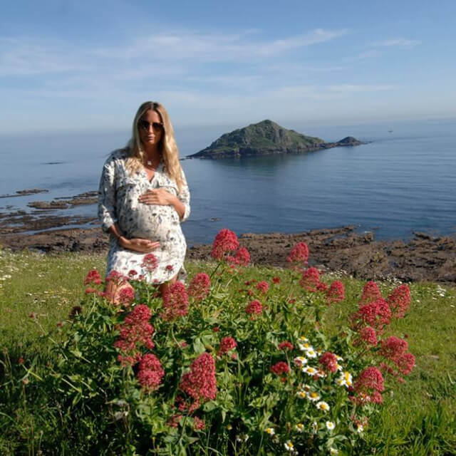pregnant woman on beach cliff top overlooking island